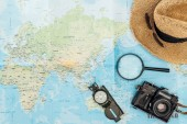 "Постер, картина, фотообои ""Top view of straw hat, compass, magnifier and film camera on world map"""