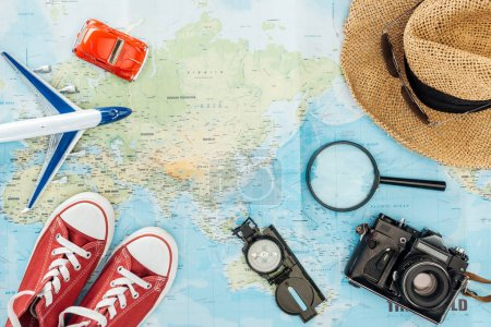 Top view of gumshoes, straw hat, magnifier, toy plane, toy car, sunglasses, film camera and compass on world map