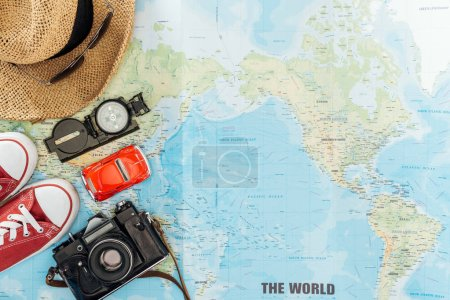 Top view of gumshoes, straw hat, sunglasses, film camera, toy car and compass on world map