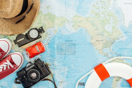 Top view of gumshoes, film camera, straw hat, sunglasses, toy car, compass and lifebuoy on world map