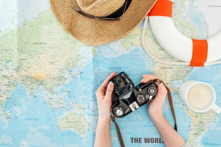 Cropped view of woman with straw hat and lifebuoy holding film camera on world map