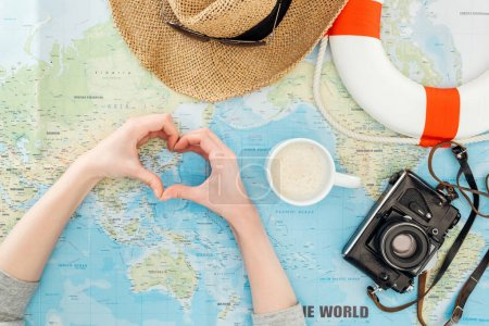 Partial view of woman with straw hat, film camera, sunglasses and lifebuoy showing heart sign on world map