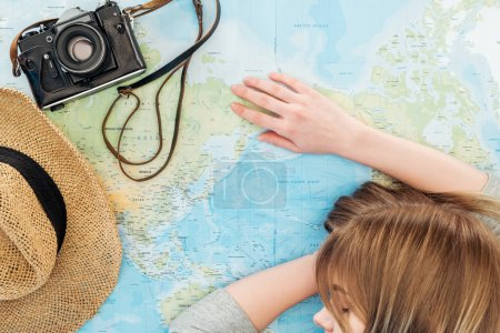 Photo pour Cropped view of woman with film camera and straw hat sleeping on world map - image libre de droit