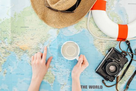Cropped view of woman with cup of cappuccino, film camera, sunglasses and straw hat pointing with finger on world map