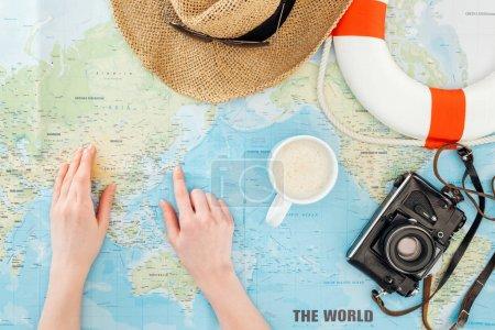 Photo pour Vue recadrée de la femme avec tasse de cappuccino, caméra de film, lunettes de soleil, bouée de sauvetage et chapeau de paille pointant du doigt sur la carte du monde - image libre de droit