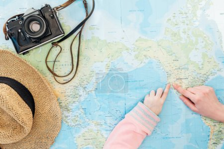 Photo pour Cropped view of child and woman with film camera and straw hat pointing with fingers on world map - image libre de droit