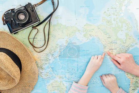 Cropped view of child and woman with straw hat and film camera pointing with fingers on world map