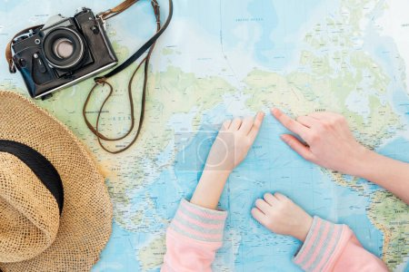 Photo pour Cropped view of child and woman with straw hat and film camera pointing with fingers on world map - image libre de droit