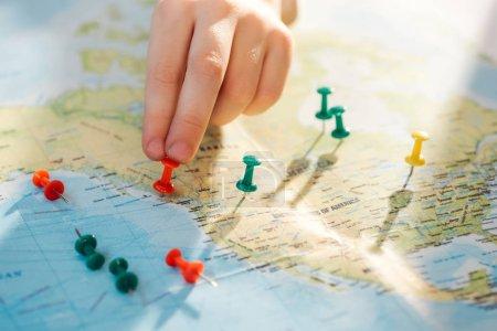 Photo pour Vue recadrée de l'homme avec des broches de poussée colorées sur la carte du monde - image libre de droit