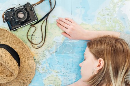 Photo pour Femme avec caméra de film et chapeau de paille dormant sur la carte du monde - image libre de droit