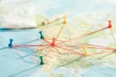 """Постер, картина, фотообои """"Selective focus of push pins and strings on world map"""""""