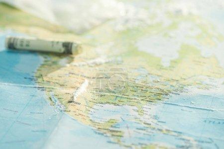 Photo pour Concentration sélective de la cocaïne et des billets en dollars sur la carte du monde - image libre de droit