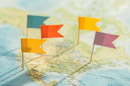 Selective focus of colorful flags and strings on world map