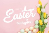 """Постер, картина, фотообои """"top view of painted chicken eggs and bright tulips on pink background with happy Easter to everyone lettering"""""""