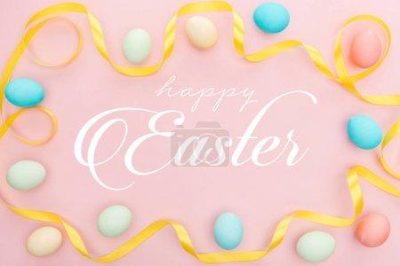 Photo pour Vue supérieure des oeufs multicolores peints de poulet et du ruban de satin sur le fond rose avec le lettrage heureux de Pâques - image libre de droit