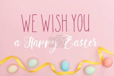 Photo pour Vue du haut des oeufs multicolores peints de poulet et du ruban de satin sur le fond rose avec nous te souhaitons un lettrage heureux de Pâques - image libre de droit