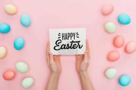 Photo for Cropped view of woman holding greeting card with happy Easter lettering near multicolored painted chicken eggs on pink background - Royalty Free Image