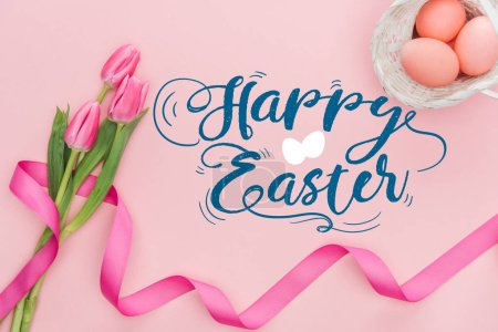 Photo for Top view of pink tulips bouquet with ribbon and painted eggs in wicker basket with happy Easter blue lettering on pink background - Royalty Free Image