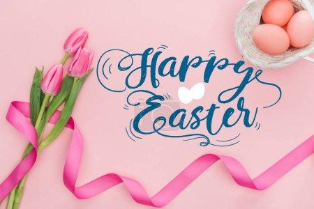 Photo pour Vue supérieure du bouquet rose de tulipes avec le ruban et les oeufs peints dans le panier en osier avec le lettrage bleu heureux de Pâques sur le fond rose - image libre de droit