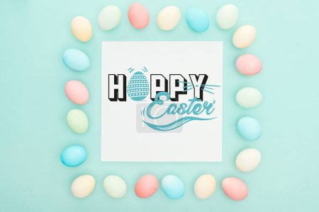 Photo for Top view of square frame made of painted chicken eggs on blue background with happy Easter lettering on white greeting card - Royalty Free Image