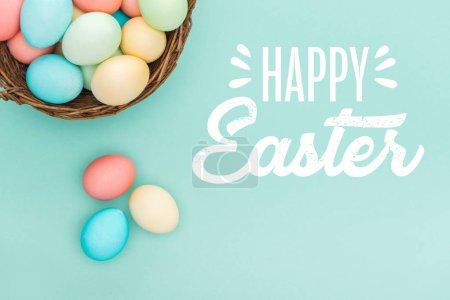 Photo for Top view of multicolored painted eggs in wicker basket with white happy Easter lettering on blue background - Royalty Free Image