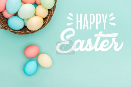 Photo pour Vue de dessus des oeufs peints multicolores dans le panier en osier avec lettrage de Pâques heureux blanc sur fond bleu - image libre de droit