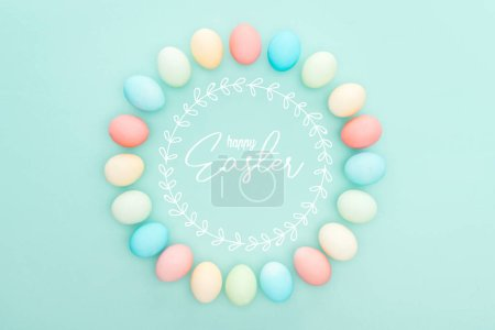 Photo for Top view of round frame made of painted chicken eggs on blue background with happy Easter lettering - Royalty Free Image