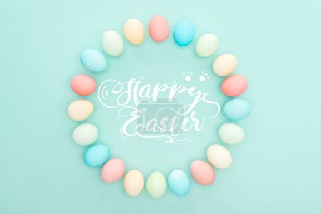 Photo for Top view of round frame made of painted chicken eggs on blue background with white happy Easter lettering - Royalty Free Image
