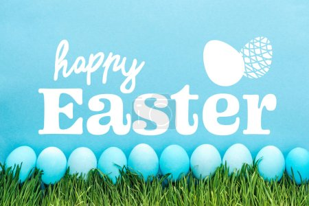 Photo for Blue painted chicken eggs on green grass with happy Easter white lettering on blue background - Royalty Free Image