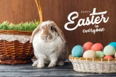 """Постер, картина, фотообои """"cute bunny near wicker baskets with green grass and colorful chicken eggs with happy Easter to everyone lettering on wooden background"""""""