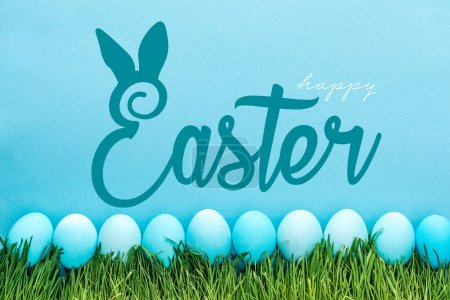 Photo for Blue painted chicken eggs on green grass with happy Easter lettering on blue background - Royalty Free Image