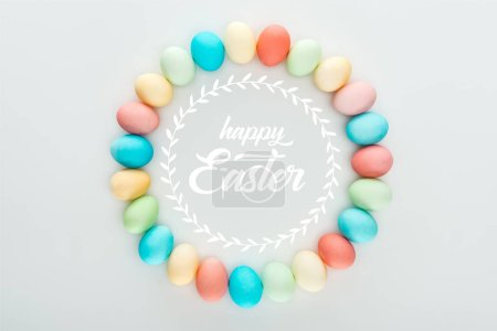 Photo for Top view of round frame made of painted multicolored eggs with happy Easter white lettering - Royalty Free Image