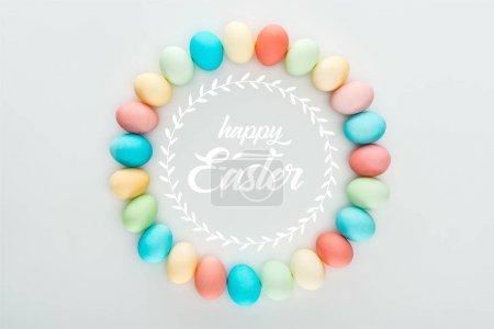 Photo pour Vue du dessus du cadre rond en œufs multicolores peints avec un lettrage blanc de Pâques heureux - image libre de droit