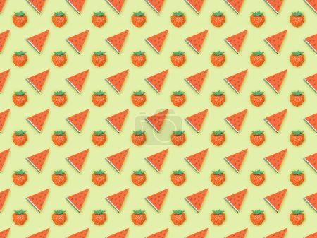 Foto de Top view of textured pattern with handmade paper strawberries and watermelon slices isolated on green - Imagen libre de derechos