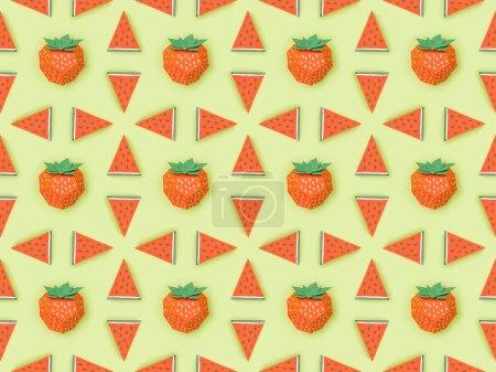 Foto de Vista superior del patrón con fresas de papel rojo hechas a mano y rodajas de sandía aisladas en verde - Imagen libre de derechos
