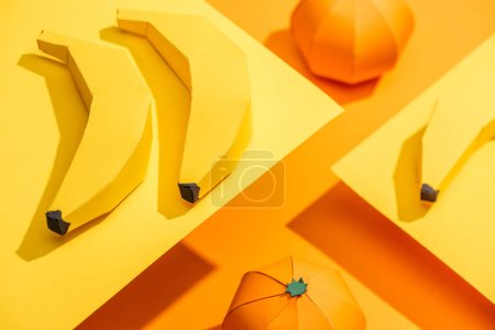 Selective Focus of origami bananas on yellow paper with tangerines on orange