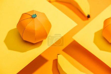 Foto de Selective Focus of paper tangerine on cardboard with origami bananas on orange - Imagen libre de derechos