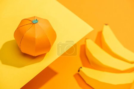 Selective Focus of origami tangerine on yellow paper with cardboard bananas on orange