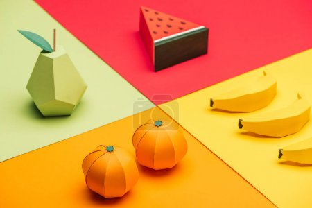 origami watermelon, pear, tangerines and bananas on colorful paper