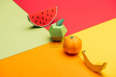 origami watermelon, apple, tangerine and banana on colorful paper