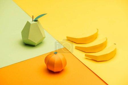 Handgemachte Origami-Birne, Bananen und Mandarine auf buntem Papier