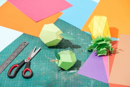 Photo pour Origami fruits and colorful cardboard with scissors and ruler on messy surface - image libre de droit