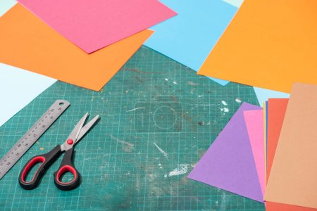 Photo for Colorful cardboard with scissors and ruler on messy surface - Royalty Free Image
