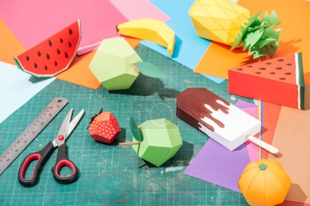 Photo for Origami fruits and colorful cardboard with scissors and ruler on messy surface - Royalty Free Image