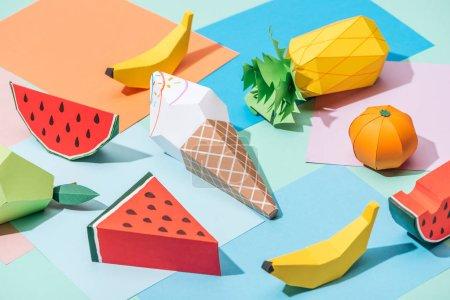 Foto de Origami ice cream and handmade cardboard fruits on multicolored paper - Imagen libre de derechos