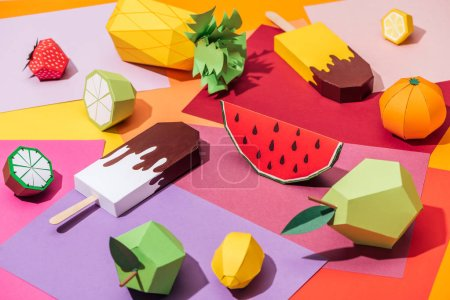 origami ice cream and handmade cardboard fruits on multicolored paper