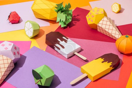 Origami ice cream and handmade cardboard fruits on...