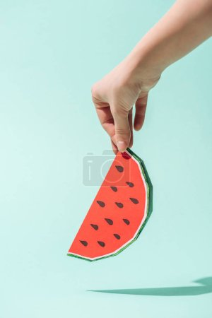 Photo for Partial view of young woman holding paper watermelon with seeds on turquoise - Royalty Free Image