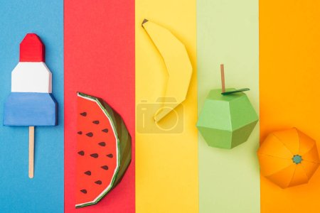 Foto de Top view of various origami fruits and ice cream on colorful paper stripes - Imagen libre de derechos