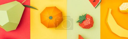 panoramic shot of various origami fruits on multicolored paper stripes